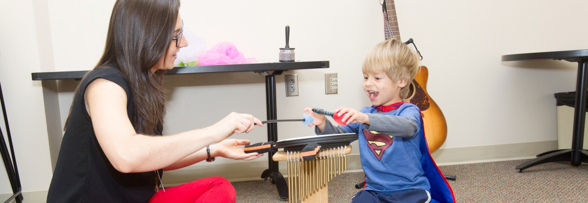 Student and young boy playing musical instruments together