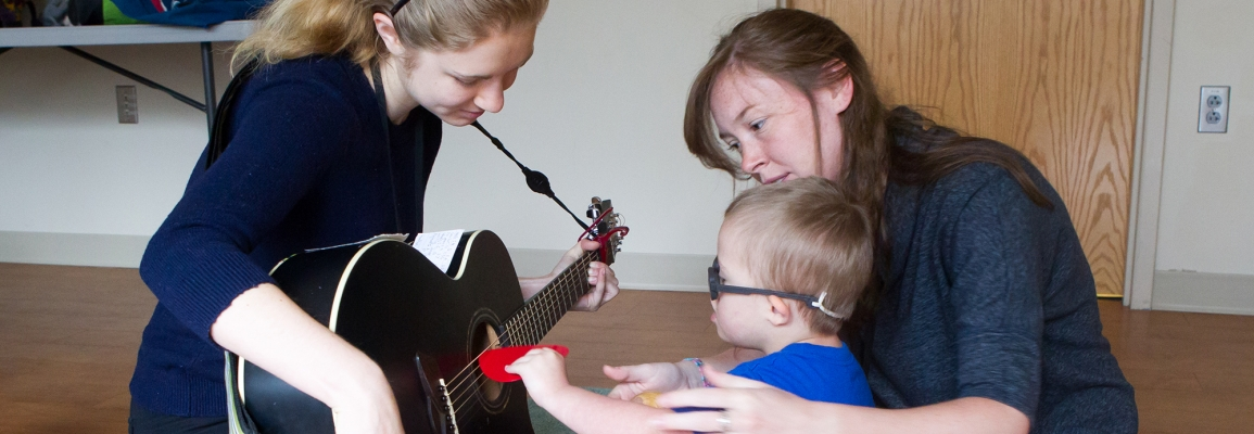 Two students, one with guitar, working with a toddler patient